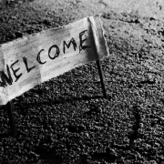 """Welcome"" written on a piece of fabric, attached to a stick at either end with the sticks in the ground to create a sign"
