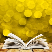 open book on table seen in profile from the bottom with bright yellow lights in the background, blurred so they look like circles