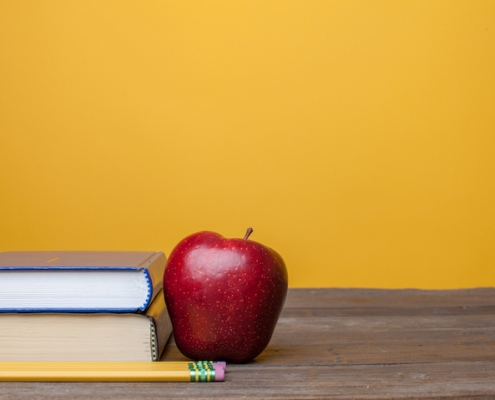 books a red delicious apple and pencil on a plain wooden table with a plain background