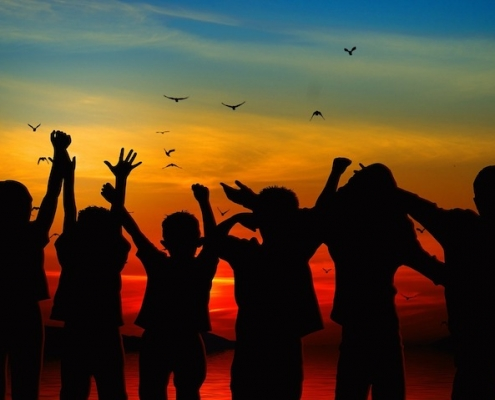 silhouettes of six children facing a sunset over water with hands raised and birds in the sky above