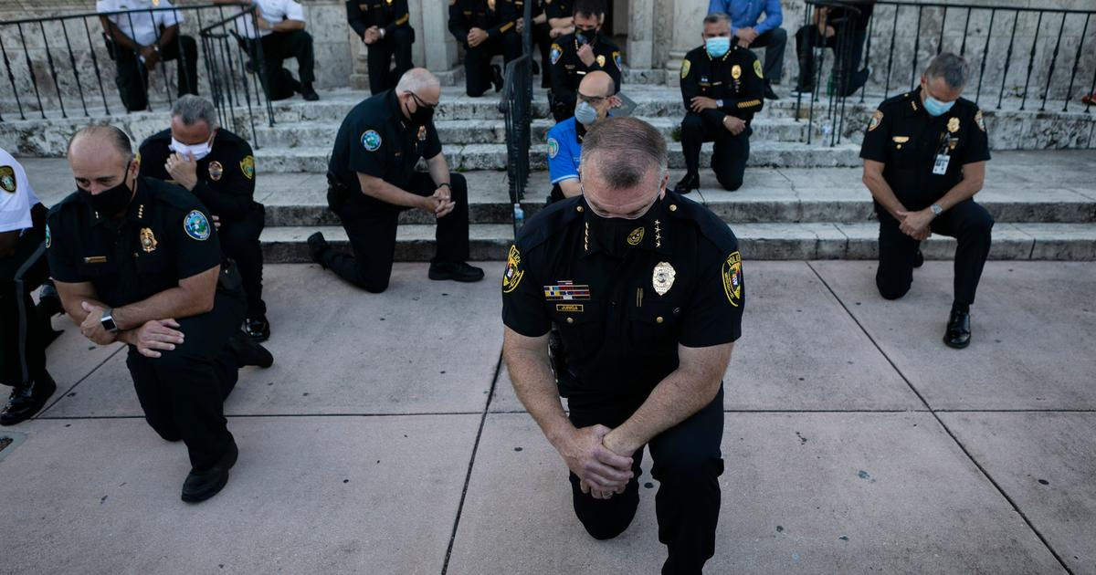 Police officers kneel during a rally in Coral Gables, Florida, May 30, 2020 Photo by Eva Marie Uzcategui/AFP via Getty Images